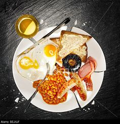 A full breakfast containing bacon, eggs, sausage, baked beans, mushroom and toast © Peter Thiedeke / Alamy