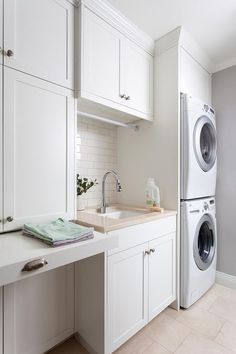 Chic laundry room features an enclosed stacked washer and dryer placed next to a sink and gooseneck faucet placed under a tension drying rod. Chic laundry room boasts white shaker cabinets fitted with a pull out folding station.