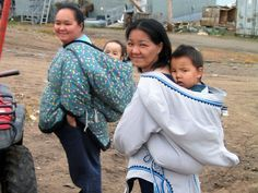 Inuit women carrying their kids in traditional hooded parkas.