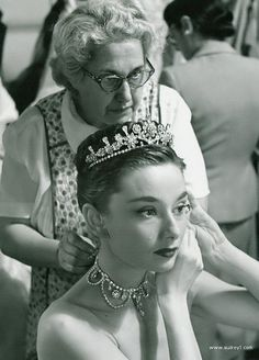 "rareaudreyhepburn: "" Audrey Hepburn (with Edith Head in the background) puts on her tiara and necklace while on the set of Roman Holiday, 1952 "" Divas, Golden Age Of Hollywood, Vintage Hollywood, New Look Dior, Estilo Lady Like, Audrey Hepburn Photos, Audrey Hepburn Roman Holiday, Aubrey Hepburn, Ideas Joyería"