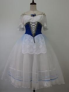 """This charming peasant Romantic tutu is created for roles like """"Coppelia"""", """"La Fille Mal Gardee"""" and """"Giselle"""". The white cotton bodice features an open oval neck with clear straps and little sleeves f"""