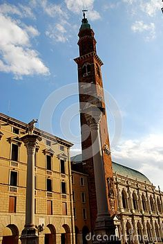 Photo taken at the Palladian Basilica in Vicenza in Veneto (Italy). In the picture you see two facades, the first yellow color that is the background to the column with the statue, the second of the great historic and beautiful building, overlooking the square, lit by the sun in the city center. Between the two buildings we see the slender bell tower with clock that penetrates into the blue sky speckled with white clouds.