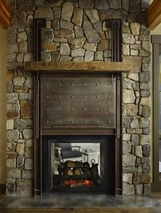 A solid metal screen, worked with pullies and chains, pulls up to reveal a flat-screen TV over the fireplace. Almost as arresting is the vie...