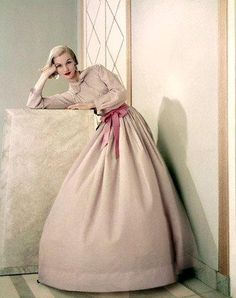 Model wearing pink dinner shirt tucked into light full skirt in sheer cotton chambray, by Claire McCardell, May 1955. Photo by Frances McLaughlin-Gill Image by © Condé Nast Archive