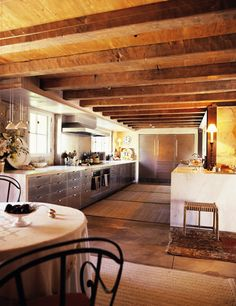 Ultra modern Kitchen with heavy wood beams, wood flooring and stainless steel drawers and large refrigerators this is like industrial kitchen
