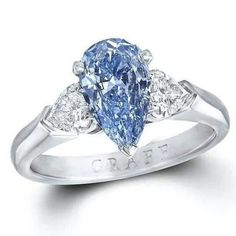 Graff 1.04ct Internally Flawless blue diamond engagement ring flanked by two pear-shaped white diamonds.