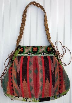 Southwestern Navajo Print Fashion Bag  The Ave Bag is one of our personal Favorites! It is Made with a vintage beach towel, vintage wall hanging (the giant kind that had wildlife as the main scene), re-purposed belt and gold colored fabric. The inside structure of the bag is made with recycled materials as well that give it structure but maintain the soft feel of the bag. The sides are adjustable to allow extra room when needed. 1 inside pocket