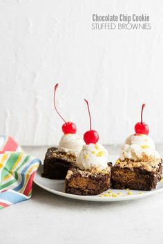 Freshly baked Chocolate Chip Cookie Stuffed Brownies with a scoop of vanilla ice cream and cherries on a white plate with striped napkin (allergy-friendly, gluten-free) BoulderLocavore.com @enjoylifefoods #ad