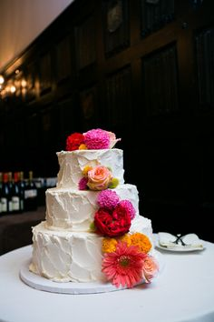 Three-tiered buttercream-frosted cake decorated with colorful flowers {Images by Berit}
