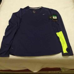 XL Women's Nike dri fit shirt Women's XL Nike running dri fit long sleeve shirt.This is a slim fit so it fits against your skin so it pulls away sweat to keep you dry and comfortable and warm.Also has the thumb holes (pic 4).This is a wonderful running shirt.Color is a dark blue with gray and neon green on the sleeves.NWT.Retail is 90.00 Nike Tops