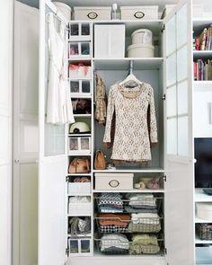 une armoire de rangement blanche avec des tiroirs et boîtes