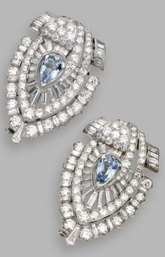 Pair of diamond and aquamarine clip-brooches, circa 1935. Of modified openwork shield-shape, set with two pear-shaped aquamarines, accented by 120 round and 76 baguette and tapered baguette diamonds, mounted in platinum. MADAME X .....