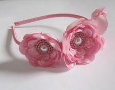 Tiara forrada com fita de cetim, com três flores de cetim rosa de diferentes tamanhos, com miolo bordado de miçangas.