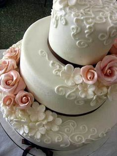 I like the subtle pairing of the all white cake and design with an accent of pink roses on this cake.