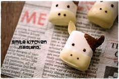 Marshmallow cows. Page is in Japanese, but it looks like if you smash down the marshmallow to make it more oval and dip one side in white chocolate to make the nose. Use almond slivers for ears and dip one corner into milk chocolate.