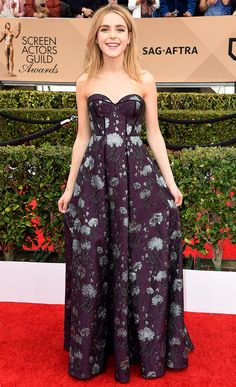KIERNAN SHIPKA wears a violet-and-silver brocade gown with a sweetheart neckline and black piping, plus Dana Rebecca Designs earrings, Irene Neuwirth rings and a natural beauty look.