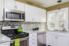 Such a stylish & sleek kitchen #tilebacksplash  #stainlesssteel MLS:15062146