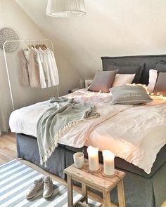Als was ein Hocker alles zu gebrauchen ist! Hier wird der rustikale Holzhocker mal eben zum Beistelltisch für die stimmungsvolle Dekoration umfunktioniert. Auch als Nachttisch macht sich der Hocker wunderbar als Ablage für kleine Accessoires, Lampe und die Gute-Nacht Lektüre. // Schlafzimmer Bett Kleiderstange Ideen Hocker Kerzen Grau Pastell #SchlafzimmerIdeen @dekogefluester