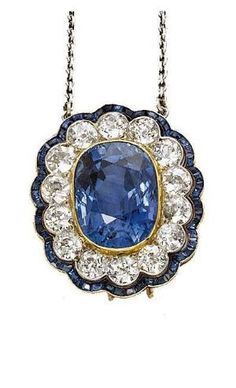 AN ART DECO SAPPHIRE AND DIAMOND PENDANT The central oval-shaped sapphire within an old-cut diamond cluster surround, to the calibré-cut sapphire scalloped border, circa 1920, pendant 3.0 cm long, with brooch fittings by shawna