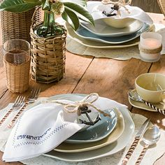 This nautical table setting was inspired by the colors found in old nautical charts, used as placemats. Vary the size of the bottles and woven patterns on the wicker casings so they look collected over time. Use twine to attach our metal anchors to the napkin. Tied with a simple bow, they're a great gift for guests. As seen in Coastal Living.