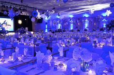 Bold blue lighting transformed this huge ballroom into a modern, elegant winter  wonderland. Huge hanging snowflakes, blue laser star projections, and snowflake gobo projections add gorgeous finishing touches.
