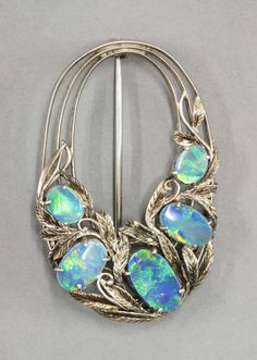 Bernard Instone (attrib.). Arts and Crafts black opal doublet brooch, c.1930. Graduated oval open open form, composed of three rows of blade edge bar, with a cluster of leaves, tendrils and five graduated black opal doublets to the lower half. Sold by Sworders.