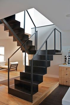 Folded plate staircase with light steel railing, having underside single center beam support.