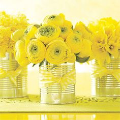 yellow ranunculus in bow-tied tins