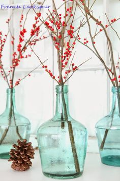 Create a simple holiday tablescape by filling vintage green vases with berry-covered branches.