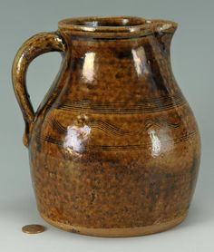 Alkaline glazed pottery pitcher, Sand Mountain, Alabama region with incised line and sine wave decoration  around upper section and pulled handle