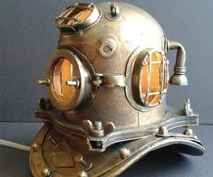 Give your home a vintage aquatic look with this custom made Scuba diver lamp. Crafted using a miniature scuba diving helmet, the interior is fitted with a small light bulb, creating a unique accent lighting that will look great anywhere you place it.