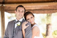 Photo of a bride and groom in San Diego, gazebo wedding photos outside in San Diego fall, bride gently wrapping her arms around her husband, groom wearing a gray suit. Cavin Elizabeth Photography