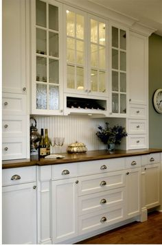 Traditional kitchen with creamy white kitchen cabinets with polished nickel pulls. White shaker cabinets with beveled butcher block countertops and white beadboard backsplash.