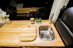 The stainless steel sink is fed by our signature water system and has a butcher block cover which doubles as a cutting board. Van Conversion Plans, Cargo Van Conversion, Sprinter Conversion, Mini Camper, Vw Camper, Vw Bus, Motorhome, Ford Transit Campervan, Campervan Interior