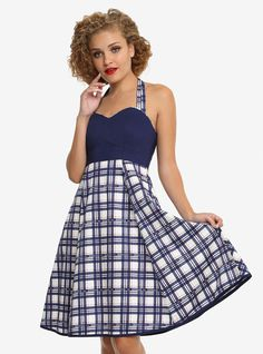 """You guys. This dress from  Doctor Who  is the epitome of wearing your fandom subtly! The halter-style dress has a bold navy bodice with a sweetheart neckline and princess seams that's trimmed in the matching plaid of the skirt and halter ties. And that plaid. Oh that plaid. It's a navy, red and cream tartan with """"Police Public Call Box"""" text design scattered throughout. The skirt is also trimmed in that same beautiful navy and has pockets to keep your Sonic Screwdriver hand..."""