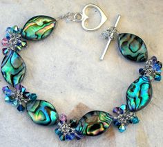 Love the heart clasp! Green Abalone Shell Bracelet, Sterling Silver, Paua Shell, Swarovski Crystals, Handcrafted Jewelry. $160.00, via Etsy.