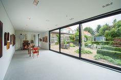 De grote glazen schuifpuien geven zicht op de bestaande woning en en de tuin.
