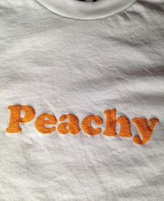 - Peachy Tee - Available in white with peachy lettering. - Sizes S, M, L - 50% Polyester, 50% Cotton