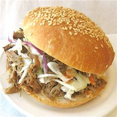 Sam's Pulled Pork with Coleslaw - slow-simmered pork and coleslaw on a homemade bun make this a devastatingly delicious sandwich.