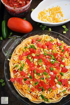 Taco Pie | by Life Tastes Good is an easy and economical recipe perfect for even the busiest nights of the week! Refried beans and seasoned ground beef sandwiched between 2 large flour tortillas is topped with shredded cheese and fresh vegetables to create a Mexican inspired dish the whole family will love! #LTGRecipes Taco Pie Recipes, Easy Casserole Recipes, Baked Chicken Recipes, Mexican Food Recipes, Cooking Recipes, Tortilla Recipes, Breakfast Recipes, Dinner Recipes, Mexican Dishes