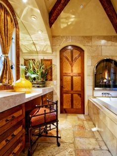 Tuscan Bathroom with fireplace, vanity and a beautiful arched doorway