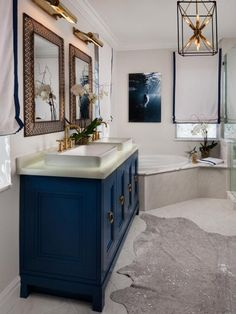 """For the master bath of a designer showhouse in Florida, designers Nicholas Skidmore and Andrew Mormile specified an aged brass finish for all the lighting. They say, """"We chose the fixtures from Hudson Valley Lighting for their classic-meets-modern style; the warm finish adds ambience and depth."""""""