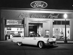 1957 Ford Thunderbird parked in front of a Ford dealership.