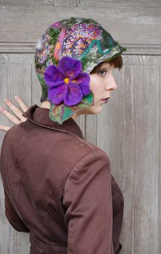Beautiful and unique felted cloche hat, retro style hat with purple flower and green leaves, purple, gray and green. Its made nuno felted technique with silk fabric and merino wool, decorated with wool fleeces, silk fibers and pieces of silk fabric. Flower isnt sewn, it was felted together with hat. Warm, light and elegant. Head circumference -ca 56 cm ( 22 inches )