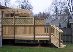 A wood deck with a trellis (pergola). Note the privacy fence with the attractive heavy duty lattice on the top. The privacy fence flows into the railing and steps.