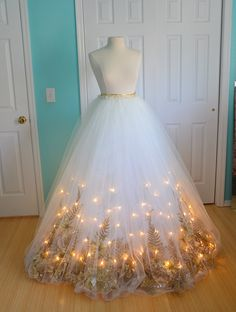 It's made from thirty yards of tulle, five yards of organza, fifteen meters of LED lights, eighteen feet of christmas garlands, wreath mesh, and fake flowers. The dress runs off of fifteen batteries, which makes it really heavy, but surprisingly easy to move around in. http://doxiequeen1.tumblr.com/post/104357530631/well-the-skirt-is-done-it-came-out-better-than-i