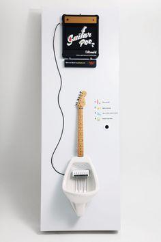 """Mictório em forma de guitarra.    A Billboard Music Brasil desenvolveu um mictório em forma de guitarra onde é possível tocar o instrumento à medida que o """"usuário"""" da engenhoca urina dentro dele.  Através de pressões diferentes em cordas diferentes posicionadas dentro do mictório, várias notas são executadas e transmitidas até um amplificador que fica localizado acima da (propriamente intitulada) Guitar Pee. E o mais legal, é possível baixar seu """"Mpee3″ depois!"""