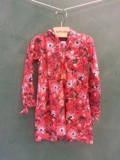 Vestido estampado com detalhe de florzinha no cordão do capuz.