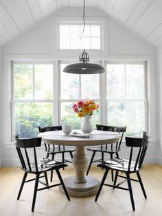 The family of four enjoys meals—as well as great views—at an antique table with Windsor-style chairs in their breakfast nook.