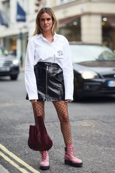 Another fine example of how to rock a patent mini: Wear with an oversized button-up, fishnets, and pink combat boots. #refinery29 http://www.refinery29.com/patent-leather-vinyl-gloss-trend-winter-2017#slide-4